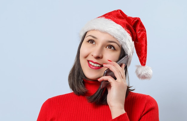 A young woman in a christmas cap and a red sweater is talking on the phone.