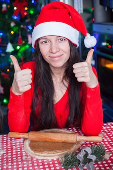 Young woman in christmas hat raised thumbs up at home