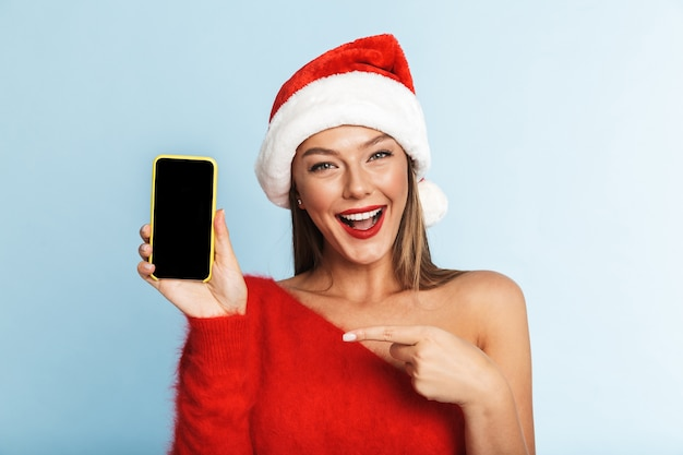Young woman in christmas hat, using mobile phone showing empty display.