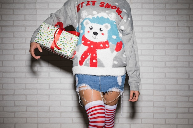 Young woman in christmas sweater with present box