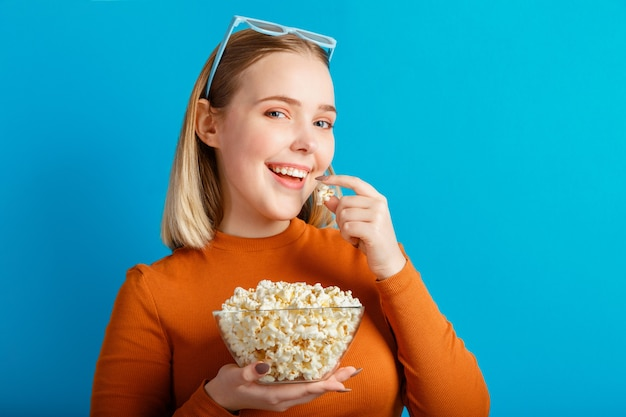 Young woman in cinema glasses. teengirl movie viewer eat popcorn isolated over blue color background