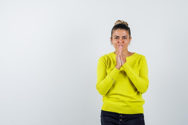 Молодая женщина, сложив руки в молитвенной позе в желтом свитере и черных брюках, выглядит серьезно