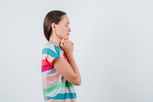 Молодая женщина, взявшись за руки в молящемся жесте в футболке и выглядя обнадеживающей.