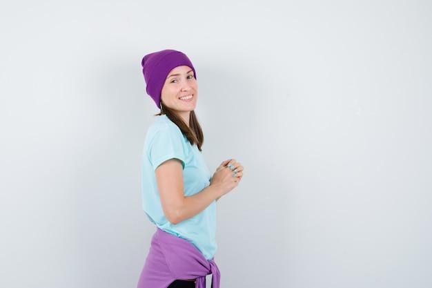 若い女性が手を握りしめ、青いtシャツ、紫色のビーニーで肩越しに見て、陽気に見える、正面図。