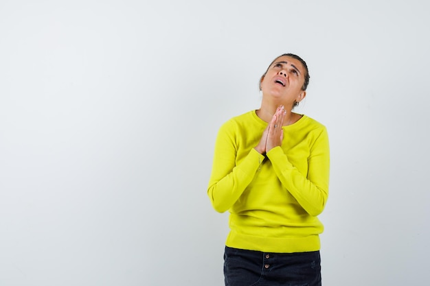 Young woman clasping hands in prayer position in yellow sweater and black pants and looking dismal