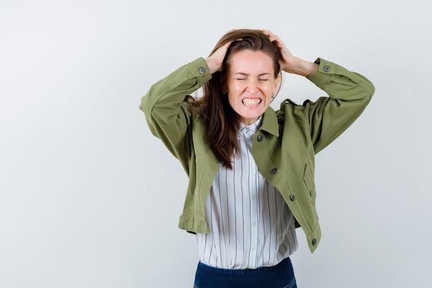 Giovane donna stringendo la testa con le mani in camicia, giacca e guardando triste, vista frontale.