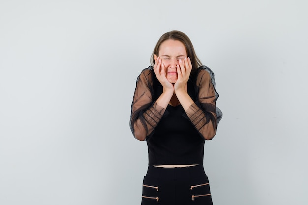 Young woman clasping her cheeks with hands in black blouse and looking uncomfortable. front view. space for text