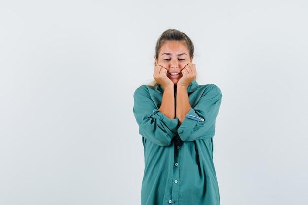 파란색 셔츠에 그녀의 주먹으로 그녀의 턱을 clasping 젊은 여자
