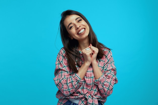 Young woman clasps hands near face smiles broadly over blue wall