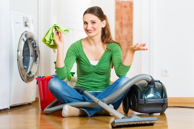 家で掃除をしている若い女性、彼女は掃除の日があり、掃除機の掃除製品とバケツを使用しています