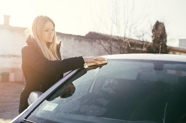 Young woman cleaning car with microfiber cloth, car detailing (or valeting) concept. selective focus on woman's hand.