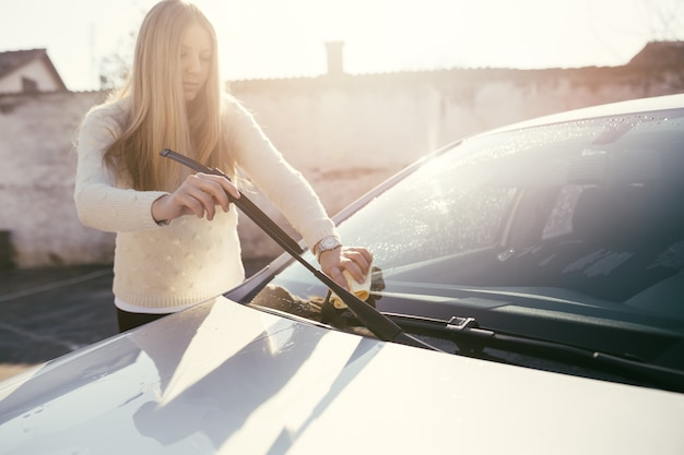 Young woman cleaning car with microfiber cloth