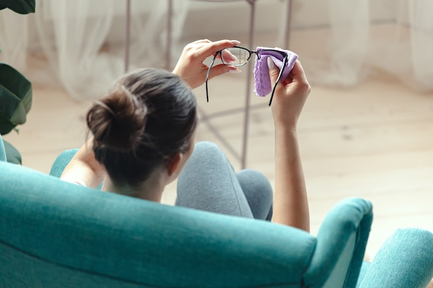 Chに座っている間ナプキンで眼鏡を掃除する若い女性