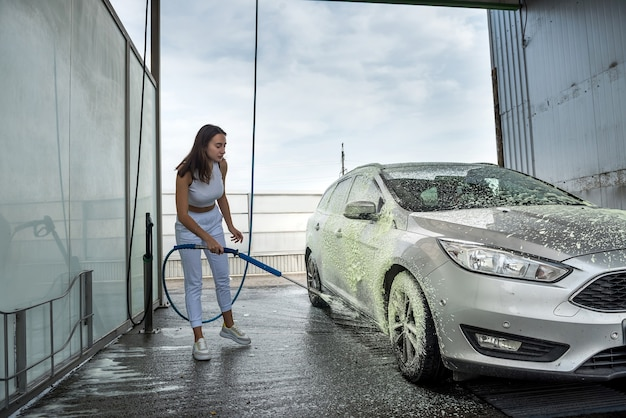 Young woman cleaning her car with hose with spray foam and pressured water at manual car washing from dirt