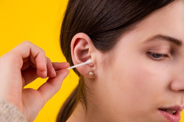 黄色の背景に綿棒で耳を掃除する若い女性