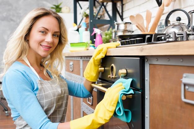 Молодая женщина, уборка в кухне, глядя на камеру