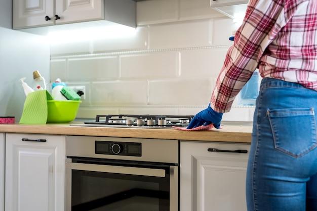 自宅のキッチンでゴム手袋とスポンジで掃除をしている若い女性。