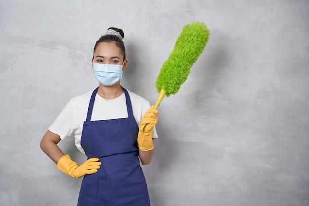のための緑のマイクロファイバーダスターを保持している医療マスクを身に着けている制服を着た女性を掃除する若い女性