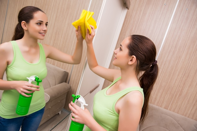 Young woman cleaning mirror at home