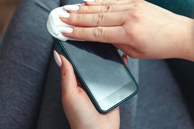 항균 응고와 휴대 전화 화면을 청소하는 젊은 여자