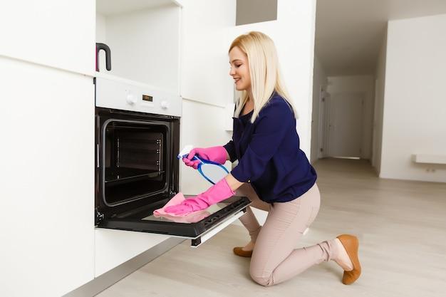 台所のオーブンを掃除する若い女性。