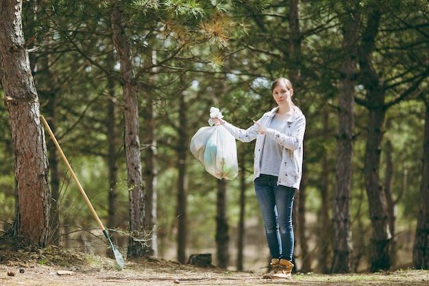 공원에서 쓰레기 봉투에 집게 손가락을 잡고 가리키는 쓰레기를 청소 하는 젊은 여자. 환경오염 문제