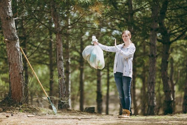 Молодая женщина убирает мусор, держа мешки для мусора и показывая жест стоп с ладонью в парке на зеленой стене