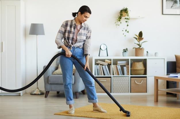 Молодая женщина чистит ковер пылесосом в комнате дома