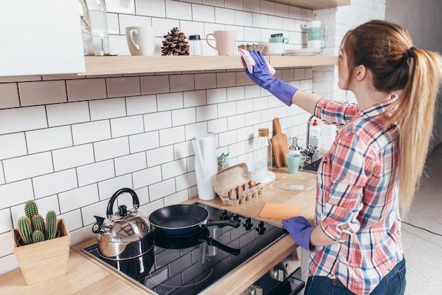 台所の家具を掃除する若い女性。
