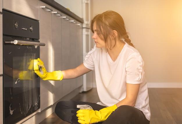 새 아파트에서 부엌 오븐을 청소하는 젊은 여성, 가사 개념 배경 사진