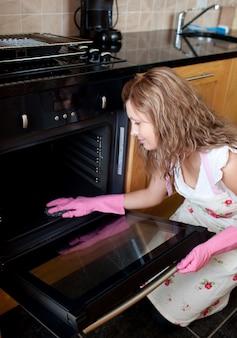오븐을 청소하는 젊은 여자