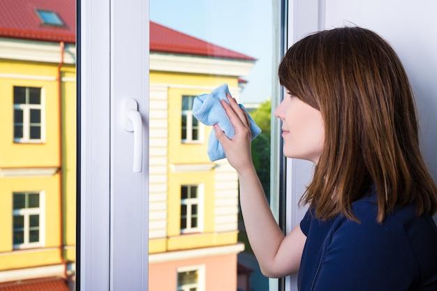 Молодая женщина, чистящая окно специальной тряпкой дома