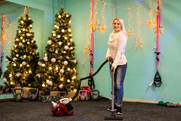 홀 룸에 있는 크리스마스 트리에서 새해 바늘을 뽑은 후 진공 청소기 바닥으로 청소하는 젊은 여성