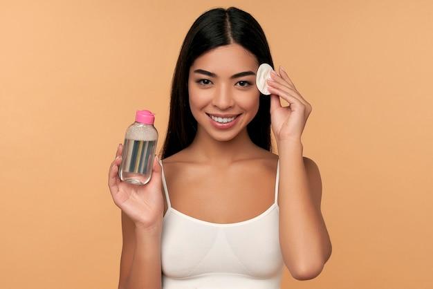 若い女性は、綿のパッドを使って顔をきれいにし、化粧水をクレンジングして化粧を落とす