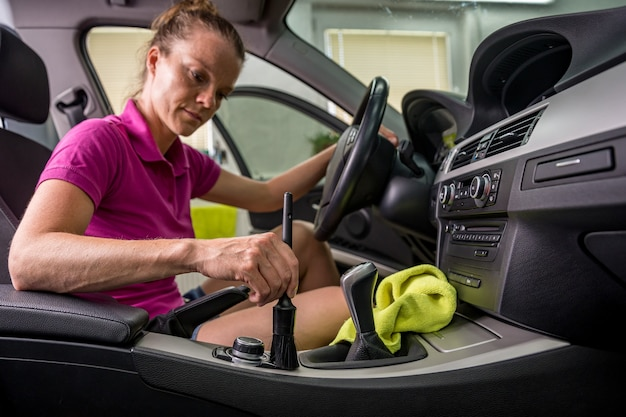 Young woman cleans the interior of the vehicle.