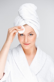 Giovane donna pulizia viso dopo il trucco