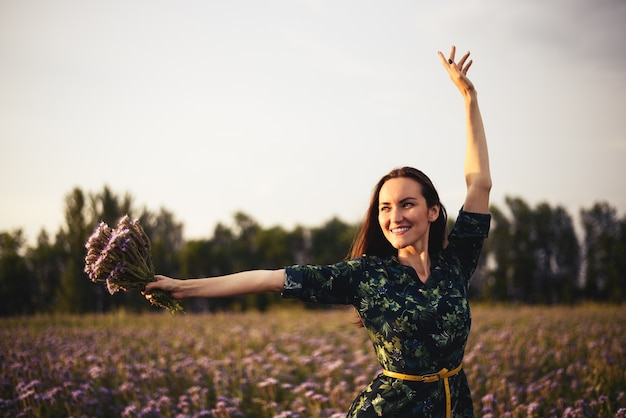 Young woman in a clearing with a bouquet of flowers smiling at sunset