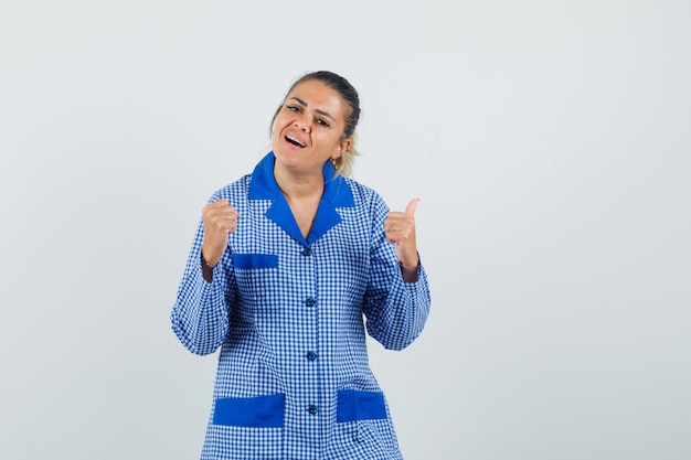 파란색 깅엄 파자마 셔츠에 엄지 손가락을 표시하고 행복을 찾는 동안 젊은 여자가 주먹을 떨림. 전면보기.