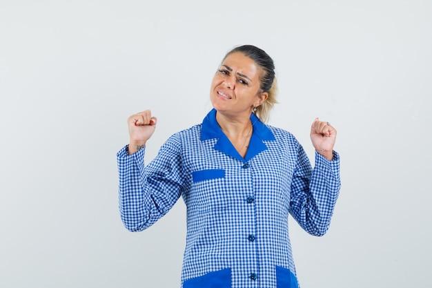 파란색 깅엄 파자마 셔츠에 주먹을 떨림과 예쁜, 전면보기를 찾고 젊은 여자.