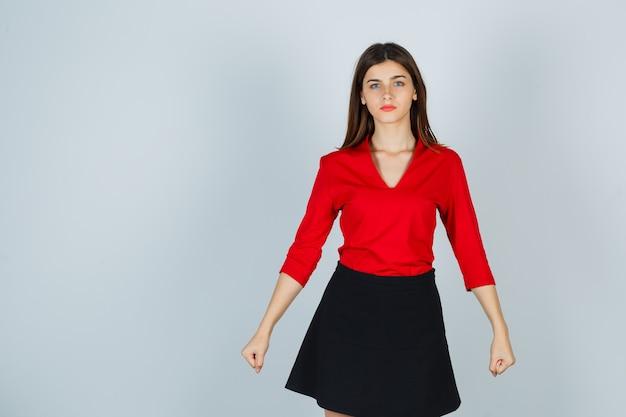빨간 블라우스, 검은 치마에 주먹을 떨림과 자신감을 찾는 젊은 여자