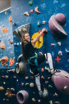 背の高い、屋内、人工のロッククライミングの壁を登る若い女性