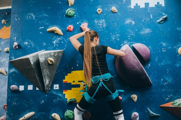 背の高い、屋内、人工のロッククライミングウォールを登る若い女性
