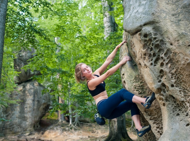 Young woman climbing on large boulders outdoor summer day