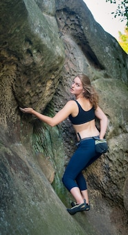 Young woman climbing on large boulders outdoor