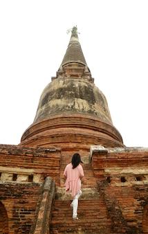 Молодая женщина поднимается по лестнице ступы древнего храма ват яй чай монгхон, таиланд