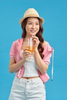 若い女性は肖像画の飲み物のジュースをクローズアップします。女性モデルの幸せな笑顔。