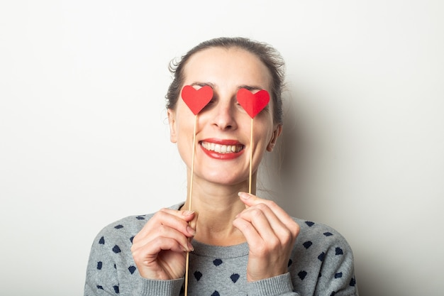 Young woman closed her eyes with hearts on sticks on a light background. valentine's day, birthday. banner.