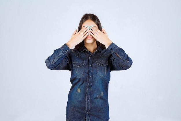 Молодая женщина закрывает глаза или часть лица и смотрит сквозь пальцы