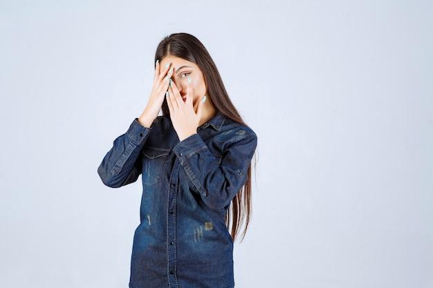 彼女の目または顔の一部を閉じて、彼女の指を通して見ている若い女性