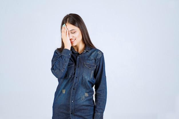 Giovane donna che chiude gli occhi o parte del viso e guarda attraverso le dita